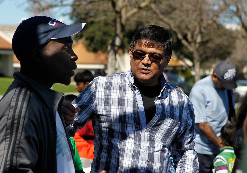 . At right, Hemant Buch, President and Founder of The California Cricket Academy speaks to cricket coach Owen Graham, left, at the cricket festival sponsored by the California Cricket Academy at the Cupertino Library Field\'s cricket pitch in Cupertino, Calif. on Saturday, March 9, 2013.  Boys and girls ages 5-13 were invited to attend and learn the basics of the game.  (LiPo Ching/Staff)