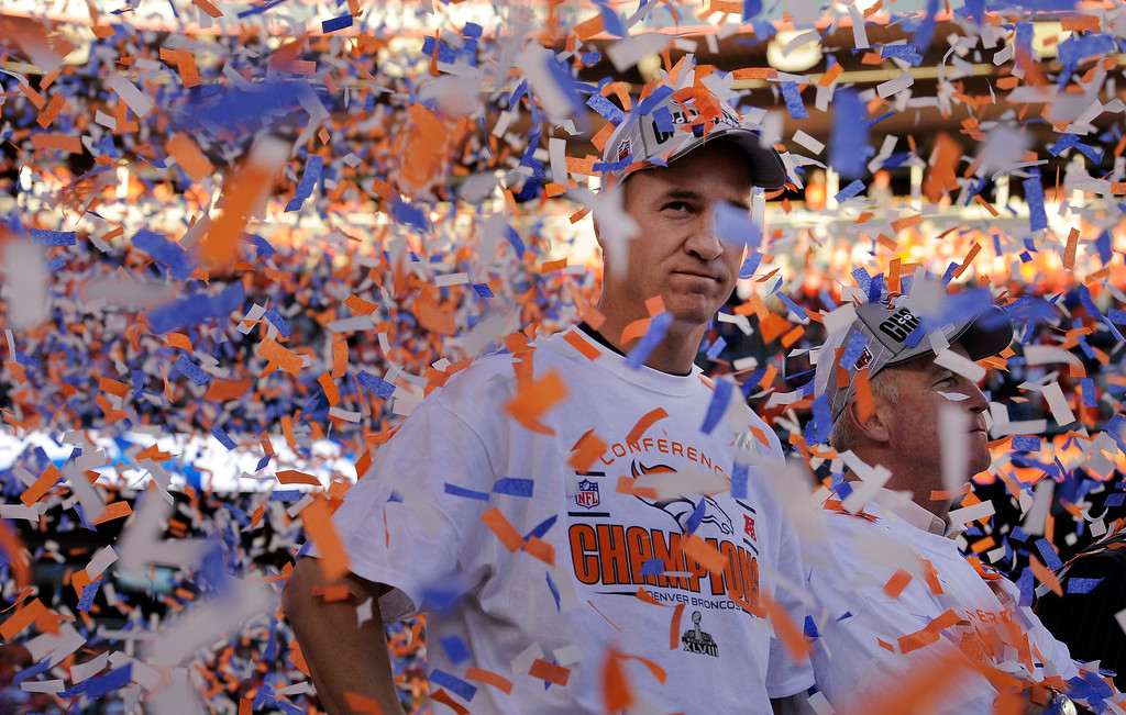 . Denver Broncos quarterback Peyton Manning (18), seems to take in the moment with Denver Broncos head coach John Fox, right, as the confetti flies all around them after the Broncos won the AFC Championship game.  T  (Photo by Helen H. Richardson/The Denver Post)