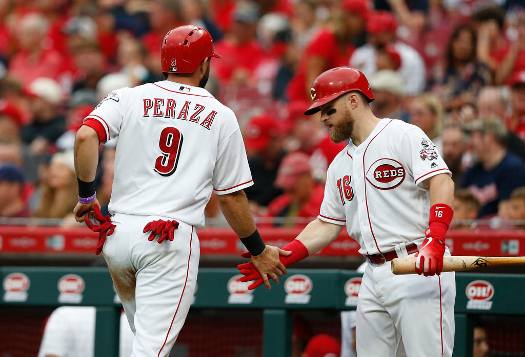 . Cincinnati Reds\' Jose Peraza (9) is congratulated by Tucker Barnhart (16) after scoring on a single by Scooter Gennett off Cleveland Indians starting pitcher Shane Bieber during the first inning of a baseball game Wednesday, Aug. 15, 2018, in Cincinnati. (AP Photo/Gary Landers)