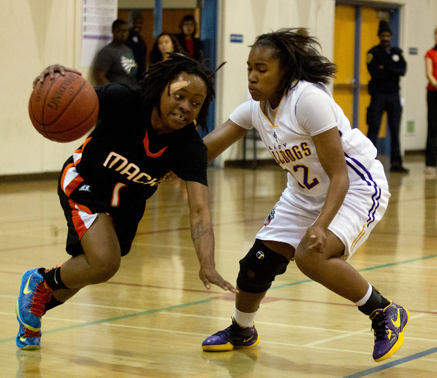 . McClymonds High School\'s Gabby Gaines, left, tries to escape defensive pressure from Oakland Technical High\'s Jayoni Lewis during the first quarter of their Oakland Athletic League girls\' basketball game, Wednesday, Feb. 20, 2013 in Oakland, Calif. McClymonds won, 62-50. (D. Ross Cameron/Staff)