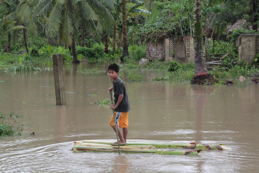 Description of . A boy rides on a makeshift raft made from banana tree as he makes his way through their flooded home after heavy rans and strong winds brought about by Typhoon Bophal hit Pantukan town, Compostela Valley province in southern island of Mindanao on December 4, 2012. Typhoon Bopha smashed into the southern Philippines early December 4, as more than 40,000 people crammed into shelters to escape the onslaught of the strongest cyclone to hit the country this year.  AFP PHOTOSTR/AFP/Getty Images