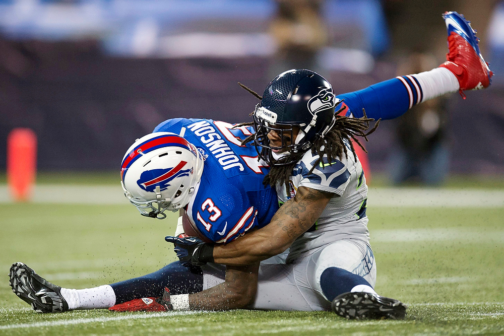 . Buffalo Bills wide receiver Stevie Johnson (13) is tackled by Seattle Seahawks cornerback Richard Sherman (25) during the first half of an NFL football game, Sunday, Dec. 16, 2012, in Toronto. The Seahawks won 50-17. (AP Photo/The Canadian Press, Frank Gunn)