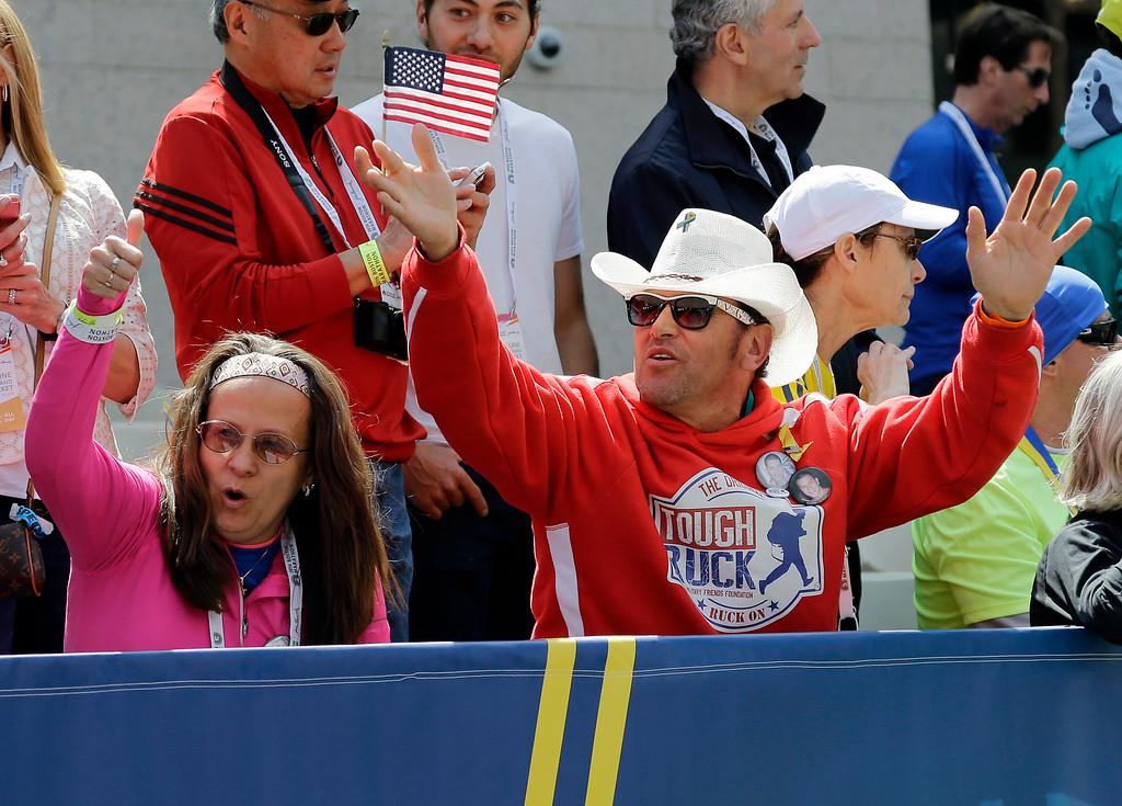 . Carlos Arredondo, right, a 2013 Boston Marathon bombing first-responder, and his wife, Melida, left, cheer runners the 120th Boston Marathon on Monday, April 18, 2016, in Boston. (AP Photo/Elise Amendola)