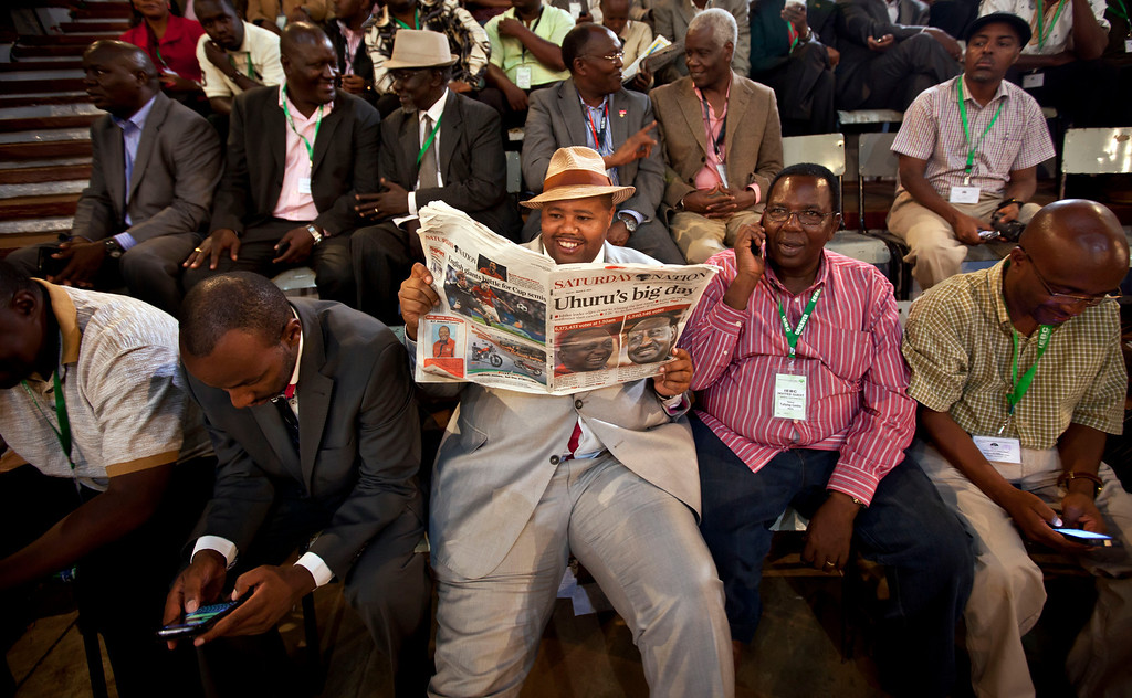 . Guests read a newspaper at the ceremony held at the National Election Center where final election results were announced declaring Uhuru Kenyatta would be the country\'s next president, in Nairobi, Kenya Saturday, March 9, 2013.  (AP Photo/Ben Curtis)