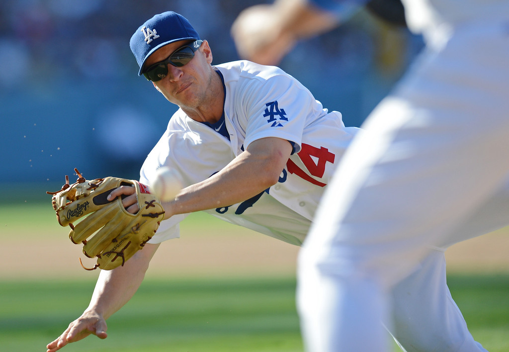 . The Dodgers\' Mark Ellis #14 makes a diving throw to 1st base as the Rockies Jonathan Herrera #18 is safe on a bunt during their game at Dodger Stadium in Los Angeles Saturday, July 13, 2013. The Dodgers beat the Rockies 1-0.(Hans Gutknecht/Los Angeles Daily News)