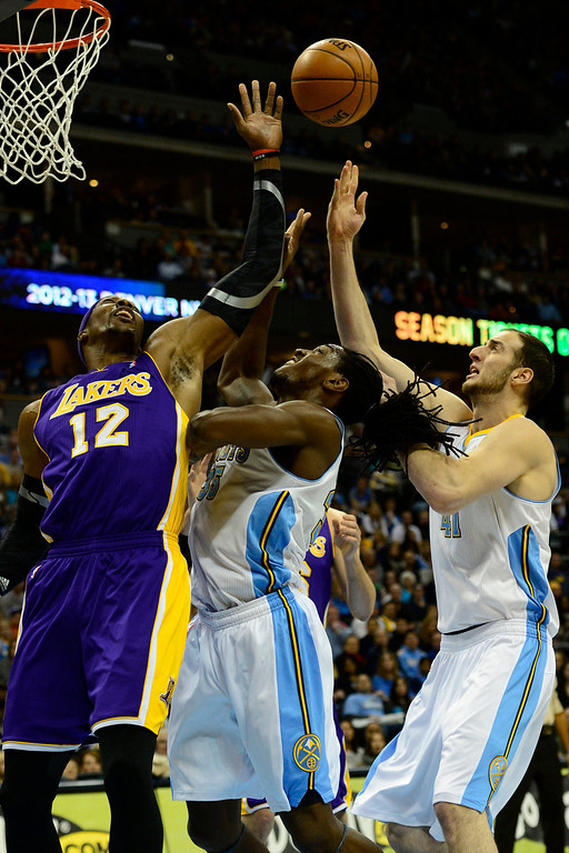 . Los Angeles Lakers center Dwight Howard (12) contends for a rebound with Denver Nuggets small forward Kenneth Faried (35) and center Kosta Koufos (41) during the first half at the Pepsi Center on Wednesday, December 26, 2012. AAron Ontiveroz, The Denver Post