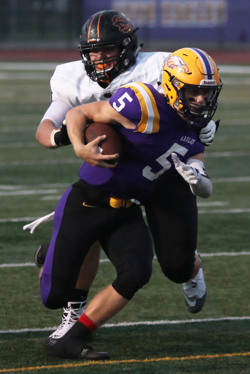. Randy Meyers - The Morning Journal<br> Avon quarterback Ryan Maloy spins away from Evan Grablovic of North Olmsted on a run during the second on Sept. 14.
