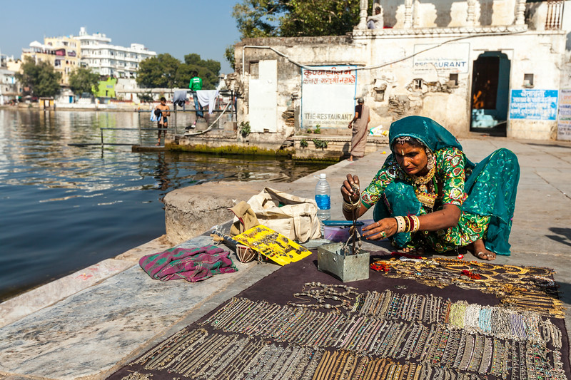 Woman in traditional clothing selling jewellery on ghat of Lake Pichola. Udaipur, Rajasthan, India