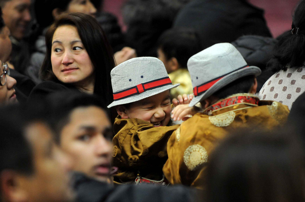. Two children play as they wait for the entrance of His Holiness the Dalai Lama as they sit on the floor with thousands form the Tibetan community. (Pioneer Press: Sherri LaRose-Chiglo)