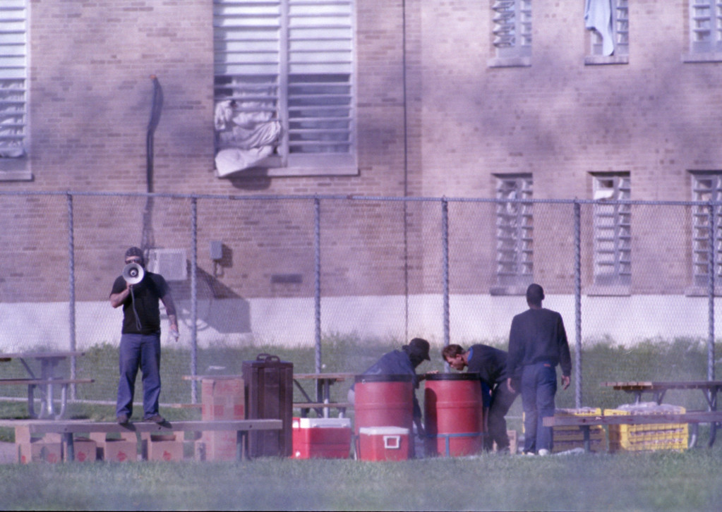 . Prisoners at the Southern Ohio Correctional Facility in Lucasville, Ohio, remove food from the recreation yard outside the cell block where they are holding five guards hostage, April 17, 1993. The food was delivered by armed guards. (AP Photo/Mark Duncan/Pool)