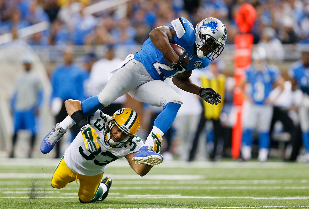 . Detroit Lions running back Reggie Bush (21) jumps over Green Bay Packers free safety Micah Hyde (33) during the first half of an NFL football game in Detroit, Sunday, Sept. 21, 2014. (AP Photo/Paul Sancya)