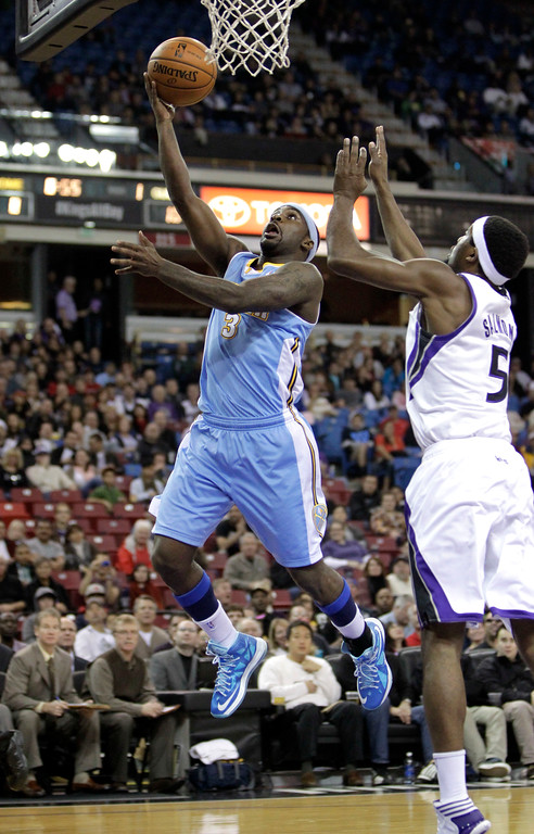 . Denver Nuggets guard Ty Lawson, left, drives to the basket against  Sacramento Kings  forward John Salmons during the first  quarter of an NBA basketball game in Sacramento, Calif., Sunday, Dec. 16, 2012.(AP Photo/Rich Pedroncelli)