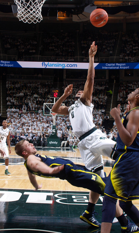 . Michigan\'s Max Bielfeldt, left, takes a charge against Michigan State\'s Marvin Clark Jr. (0) during the first half of an NCAA college basketball game, Sunday, Feb. 1, 2015, in East Lansing, Mich. Michigan State won 76-66 in overtime. (AP Photo/Al Goldis)