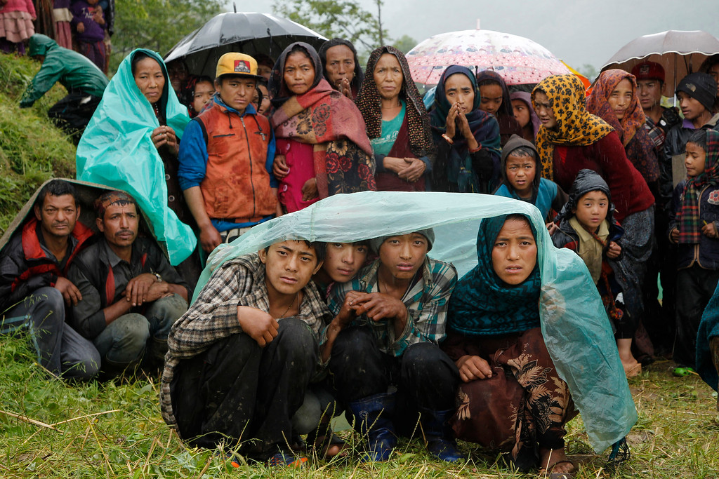 . Villagers wait in the rain as an aid relief helicopter lands at their remote mountain village of Gumda, near the epicenter of Saturday\'s massive earthquake in the Gorkha District of Nepal, Wednesday, April 29, 2015. (AP Photo/Wally Santana)