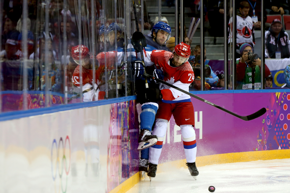. Alexander Popov #24 of Russia checks Tuomo Ruutu #15 of Finland into the boards during the Men\'s Ice Hockey Quarterfinal Playoff on Day 12 of the 2014 Sochi Winter Olympics at Bolshoy Ice Dome on February 19, 2014 in Sochi, Russia.  (Photo by Bruce Bennett/Getty Images)