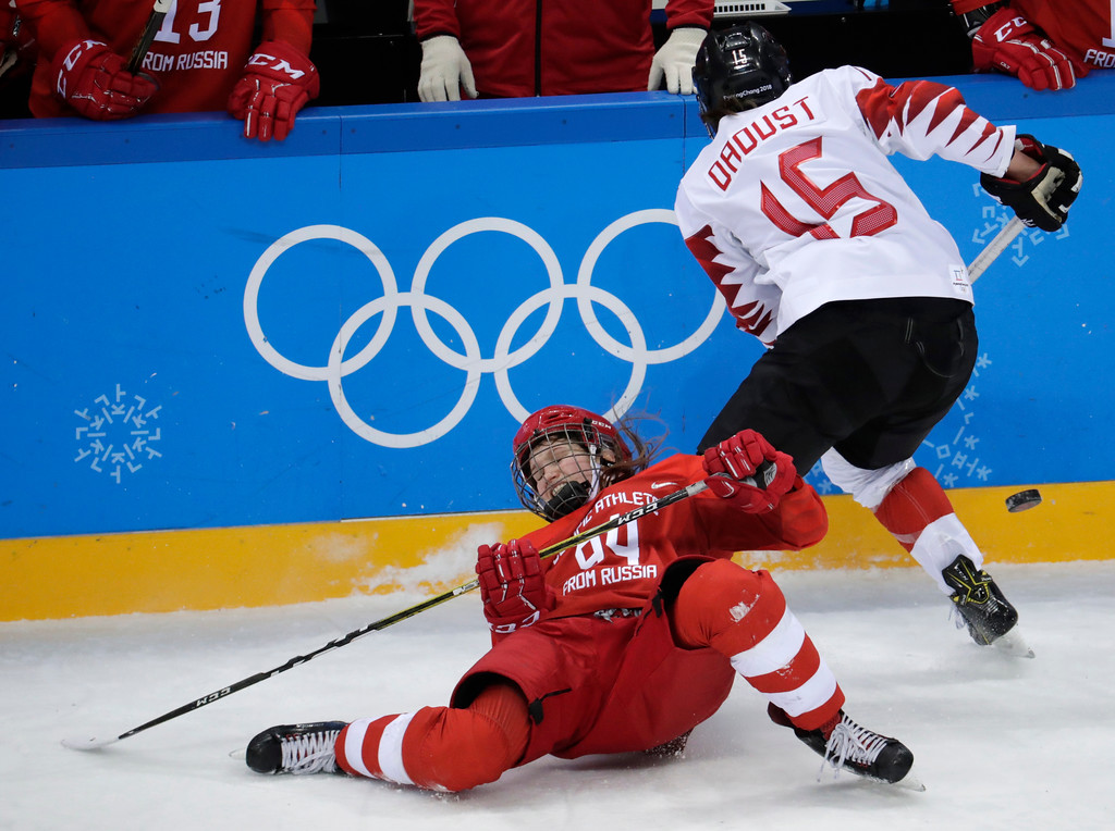 . Russian athlete Yevgenia Dyupina (94) falls as Melodie Daoust (15), of Canada, steals the puck during the third period of the semifinal round of the women\'s hockey game at the 2018 Winter Olympics in Gangneung, South Korea, Monday, Feb. 19, 2018. (AP Photo/Julio Cortez)
