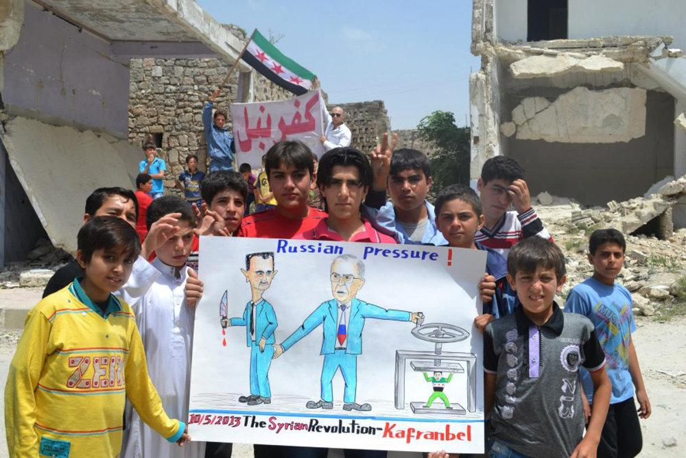 ". Anti-Syrian regime protesters hold a poster depicting Syrian President Bashar Assad, left, and Russian Foreign Minister Sergei Lavrov, right,  during a demonstration, at Kafr Nabil town, in Idlib province, northern Syria, Friday May 10, 2013. Arabic banner in the background reads, ""Kafr Nabil.\""  (AP Photo/Edlib News Network ENN)"