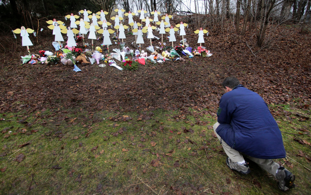 . Robert Soltis, of Newtown, Conn., pauses after making the sign of the cross at a memorial to school shooting victims in Newtown, Tuesday, Dec. 18, 2012. Adam Lanza walked into Sandy Hook Elementary School in Newtown, Dec. 14,  and opened fire, killing 26 people, including 20 children, before killing himself. (AP Photo/Charles Krupa)
