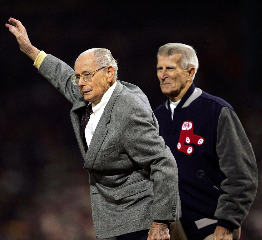 . Dom DiMaggio, left, and Johnny Pesky, both former Red Sox players, wave after throwing out the ceremonial first pitch for Game 2 of the World Series in Boston, Sunday, Oct. 24, 2004.  (AP Photo/Charles Krupa)