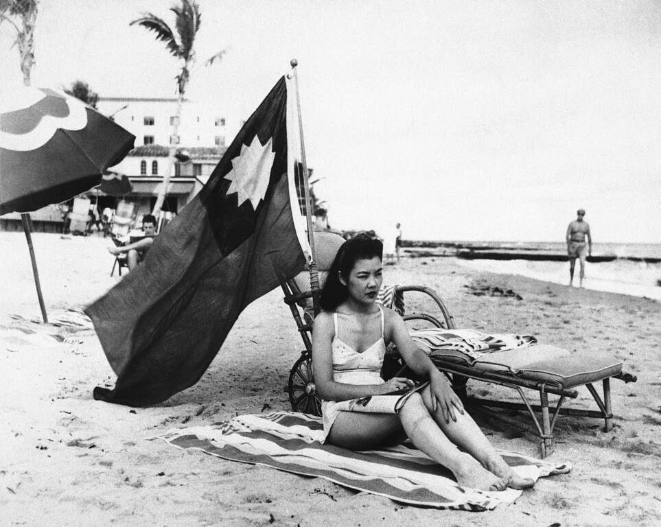 . Ruth Lee, hostess at a Miami Chinese restaurant, seen Dec. 15, 1941, doesn\'t want to be mistaken for Japanese when she sunbathes on her days off, and brings along a Chinese flag.  Miss Lee is actually American-born. (AP Photo)