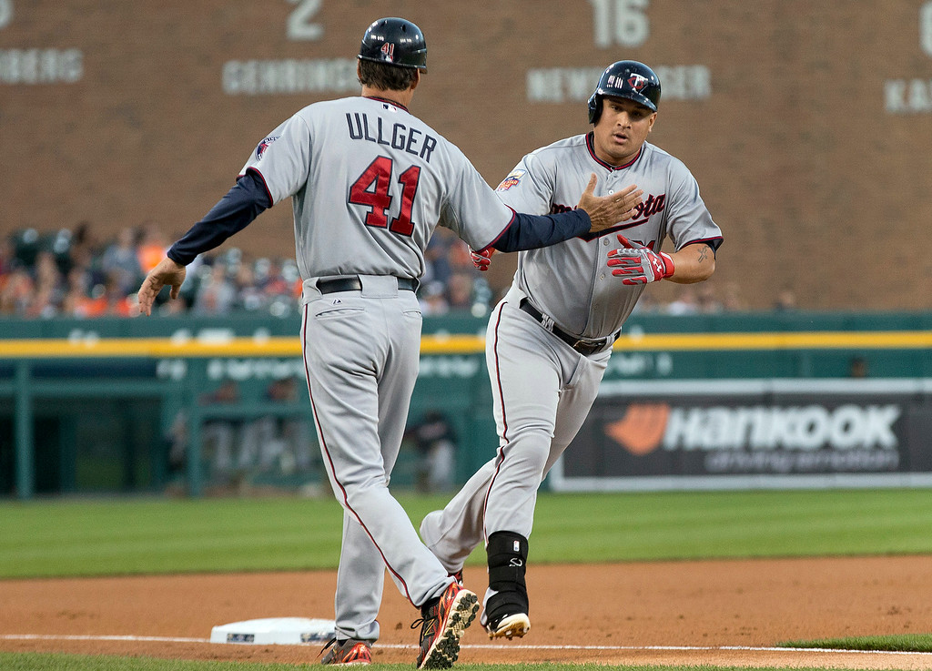 . Minnesota Twins right fielder Oswaldo Arcia celebrates his two-run home run against the Detroit Tigers with third base coach Scott Ulger (41) in the first inning of a baseball game in Detroit, Friday, Sept. 26, 2014. (AP Photo/Paul Sancya)
