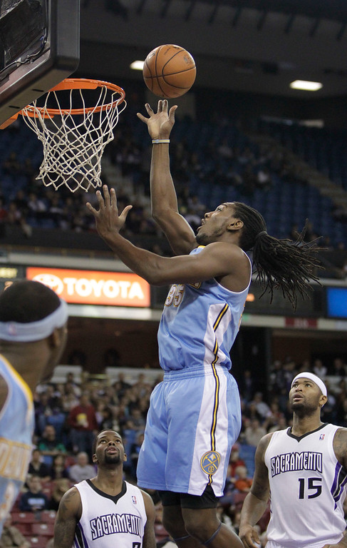 . Denver Nuggets forward Kenneth Faried, center, goes to the basket between Sacramento Kings\' Aaron Brooks, left, and DeMarcus Cousins during the first quarter of an NBA basketball game in Sacramento, Calif., Sunday, Dec. 16, 2012.(AP Photo/Rich Pedroncelli)