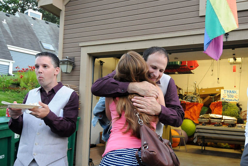 . Bradley Weber right, is hugged by friend Nicole Grzeskowiak as his fiance Ryan Pfeifle,far left, are greated by guests. (Pioneer Press: Sherri LaRose-Chiglo)