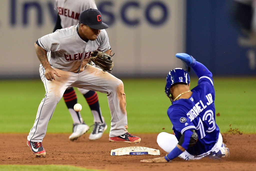 . Toronto Blue Jays second baseman Lourdes Gurriel Jr. (13) slides safely into second base as Cleveland Indians third baseman Jose Ramirez bobbles the ball during eighth inning baseball action in Toronto, Sunday, Sept. 9, 2018. (Frank Gunn/The Canadian Press via AP)