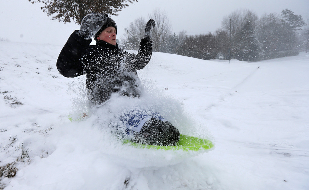 . Stephen Clark, 12, hits a ramp made of snow near as he sleds near his home in Charlotte, N.C., Wednesday, Feb. 12, 2014, as a winter storm moves into the area. (AP Photo/Chuck Burton)