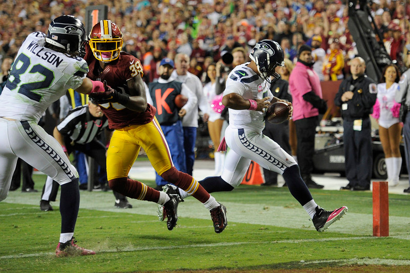 . Seattle Seahawks quarterback Russell Wilson (3) scores a touchdown on a quarterback keeper as tight end Luke Willson (82) ties up Washington Redskins cornerback David Amerson (39) during the first half of an NFL football game in Landover, Md., Monday, Oct. 6, 2014. (AP Photo/Nick Wass)