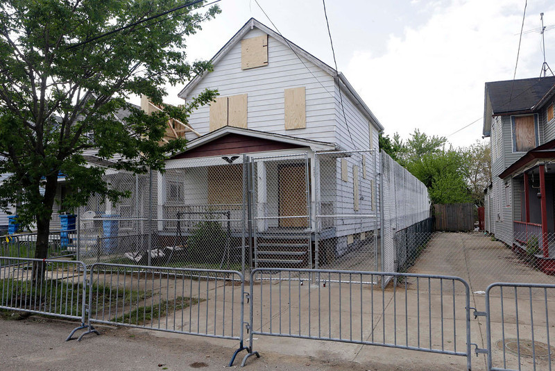 . A 10-foot chain link fence surrounds the home of Ariel Castro in Cleveland Tuesday, May 14, 2013. Castro is under arrest and charged with kidnapping and rape after three women were rescued last week at the house after being held captive for a decade.  (AP Photo/Mark Duncan)