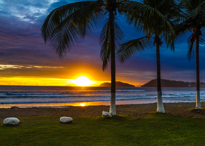 Sunset under palm trees and the beach in Jaco, Costa Rica