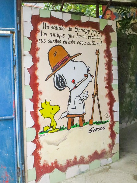 """More art at Muraleando. I believe this translates to: """"A salute by Snoopy and Woodstock for the friends who made reality from dreams in this cultural home."""""""