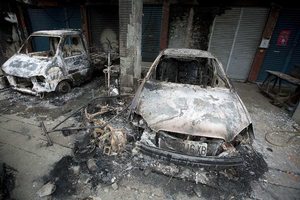 . Damaged vehicles lie on the road after gas explosions in southern Kaohsiung on August 1, 2014 in Kaohsiung, Taiwan. A series of powerful gas blasts killed 25 people and injured up to 267 in the southern Taiwanese city of Kaohsiung, overturning cars and ripping up roads, officials said.  (Photo by Ashley Pon/Getty Images)