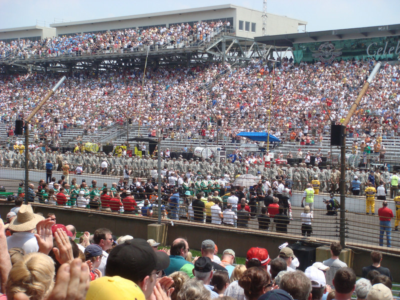 Cars and teams on the track preparing to start the 2010 Indianapolis 500.  In this picture is the final starting row. From top to bottom: Takuma Sato, Sebastian Saavedra, Tony Kanaan.