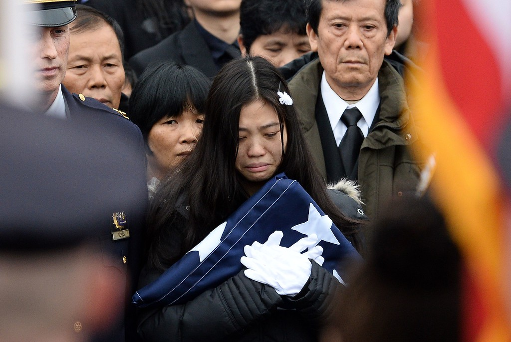 . Pei Xia Chen (C) widow of New York Police Department (NYPD) officer Wenjian Liu holds a NYPD flag as NYPD officers load her husband\'s casket for a procession during his funeral in New York\'s borough of Brooklyn on January 4, 2015. A sea of blue uniformed officers crowded around a Brooklyn funeral home to honor Wenjian Liu, 32, shot in the head with partner Rafael Ramos, 40, on December 20, 2014 as the pair sat in their patrol car. The brutal double-slaying at the hands of a black gunman claiming to be avenging the deaths of African-Americans during confrontations with police shocked the nation\'s largest city. JEWEL SAMAD/AFP/Getty Images