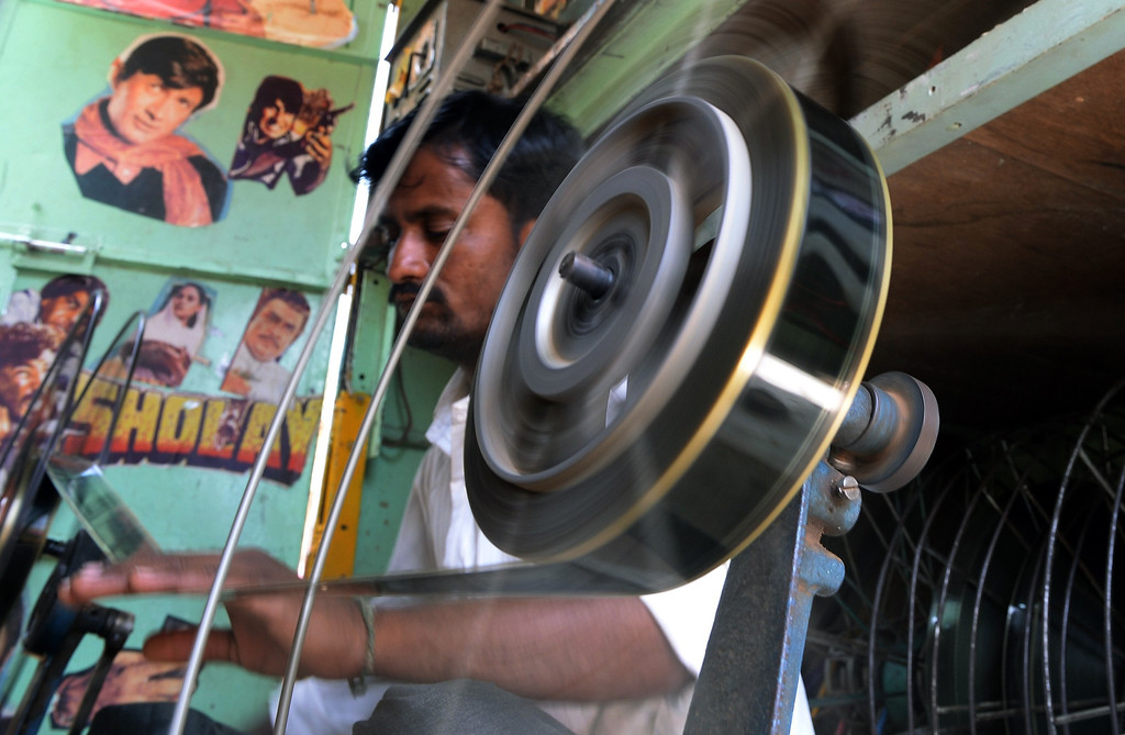 """. Indian cinema projectionist Suhas, winds film roll onto spools inside his \""""projection Truck\"""" on the premises of the Anup Touring Talkies tent cinema at a ground in central Mumbai on April 20, 2013.  To mark 100 years of Indian Cinema, a Marathi film \""""Touring Talkies\"""" is being screened in a makeshift tent theatre just like the days of yore, in its pre-multiplex and pre-single screen glory dating back 50 years. The tents, keeping in mind modern audiences, will have plush seating, air conditioning and popcorn and cola alongside fresh sugar-cane juice, roasted groundnuts and gram and pickle and other tit-bits. The cinema will screen four shows per day for a week. The idea of touring talkies was the brainchild of the doyne of Indian cinema, Dadasaheb Phalke, after he saw the British watching movies in tents. The touring cinema would travel through rural India and screen movies in makeshifts tents. At present, one can only find these talkies - whose sweltering tents and basic facilities contrast with the plush, air-conditioned multiplexes springing up in Indian cities, during Jatras (village fairs) in the interiors of the state.  INDRANIL MUKHERJEE/AFP/Getty Images"""