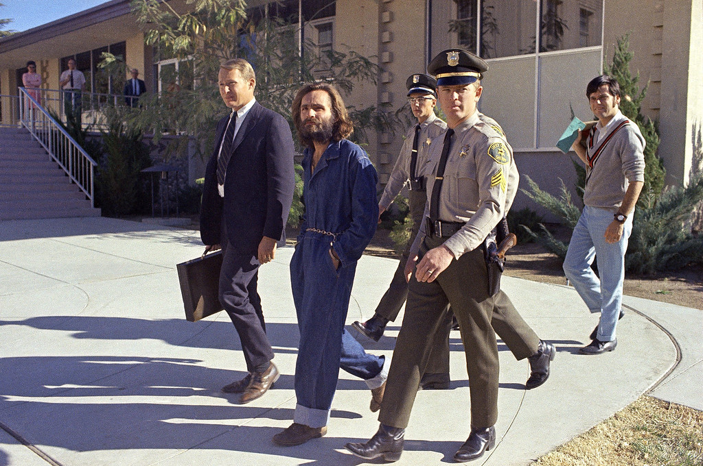 . Charles Manson is escorted by officers while en route to court in Independence, Calif., Dec. 3, 1969.  Manson and three women co-defendants were convicted and sentenced to death after the 10-month trial that involved the murders of actress Sharon Tate and six others in the hills near Hollywood, Calif.  Their sentences were later commuted to life when the death penalty was briefly outlawed. (AP Photo)