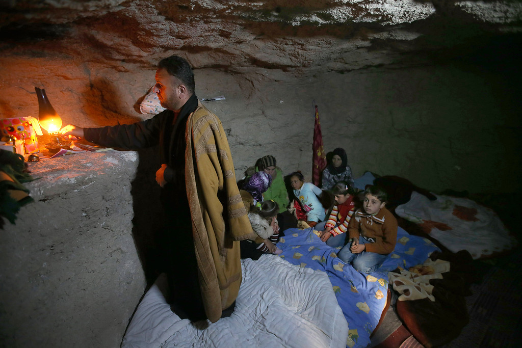 . FILE - A defected Syrian policeman, Adnan al-Hamod, 33, lights a kerosene lamp at an underground cave used for shelter from Syrian government forces shelling and airstrikes, at Jirjanaz village, in Idlib province, Syria, Thursday Feb. 28, 2013. (AP Photo/Hussein Malla, File)