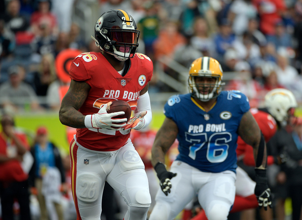 . AFC running back Le\'Veon Bell (26), of the Pittsburgh Steelers, runs the ball ahead of NFC defensive tackle Mike Daniels (76), of the Green Bay Packers, during the first half of the NFL Pro Bowl football game, Sunday, Jan. 28, 2018, in Orlando, Fla. (AP Photo/Phelan M Ebenhack)