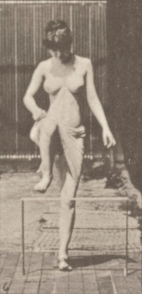 Semi-nude woman stepping over a fence