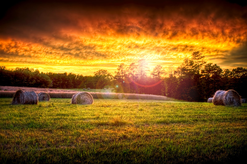 Beautiful sunset lighting a field with hay rounds producing brilliant and amazing colors.