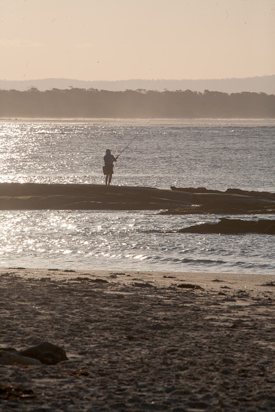 A fisherman casts from the shore of Woody Head as the sunset lights the background.