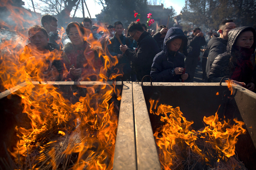 . People discard incense into a cauldron as they pray on the first day of the Lunar New Year at the Lama Temple in Beijing, Friday, Feb. 16, 2018. Chinese around the world celebrated the arrival of the Year of the Dog on Friday with family reunions, firecrackers and traditional food. (AP Photo/Mark Schiefelbein)