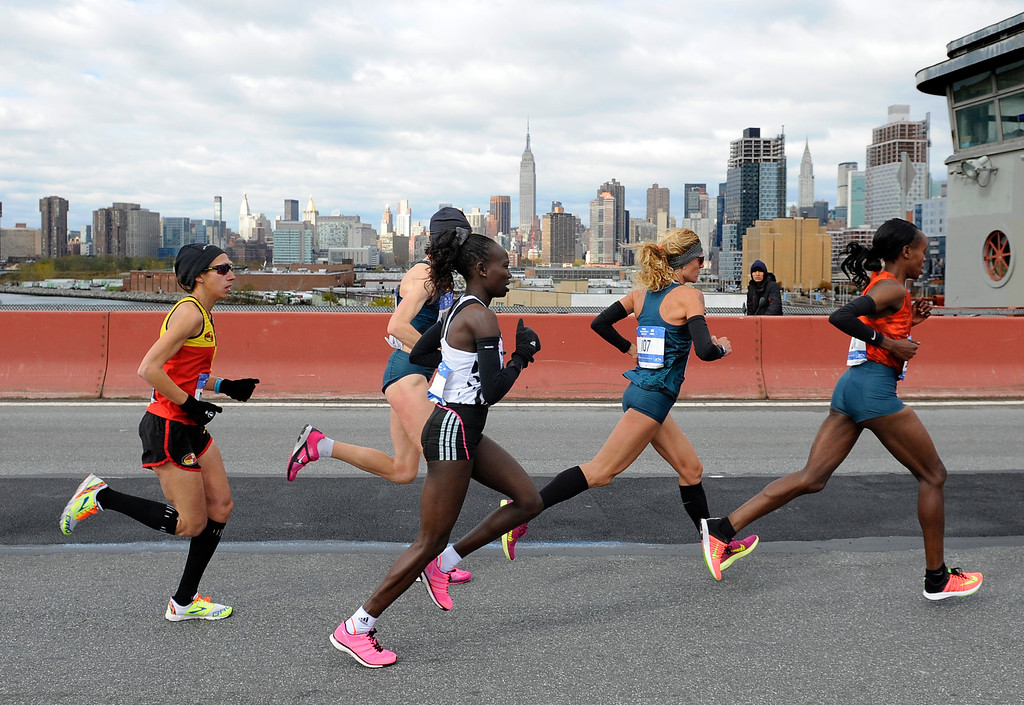 . The lead women runners cross the Pulaski Bridge to enter the Queens borough of New York during the New York City Marathon on Sunday, Nov. 2, 2014. Mary Keitany of Kenya, third from left, came in first to win the women\'s title. Jemima Sumgong, of Kenya, right, came in second. (AP Photo/Kathy Kmonicek)