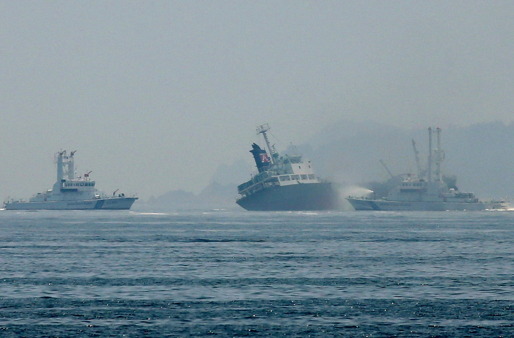 . This picture shows the 998 ton oil tanker Shoko-Maru (C) listing off the coast of Hyogo prefecture, around 450 kilometers (280 miles) west of Tokyo on May 29, 2014. A 998 ton oil tanker was listing off the Japanese coast on May 29 after an explosion and subsequent fire that sent towering columns of acrid smoke into the sky.   AFP PHOTO / JIJI PRESS       /AFP/Getty Images