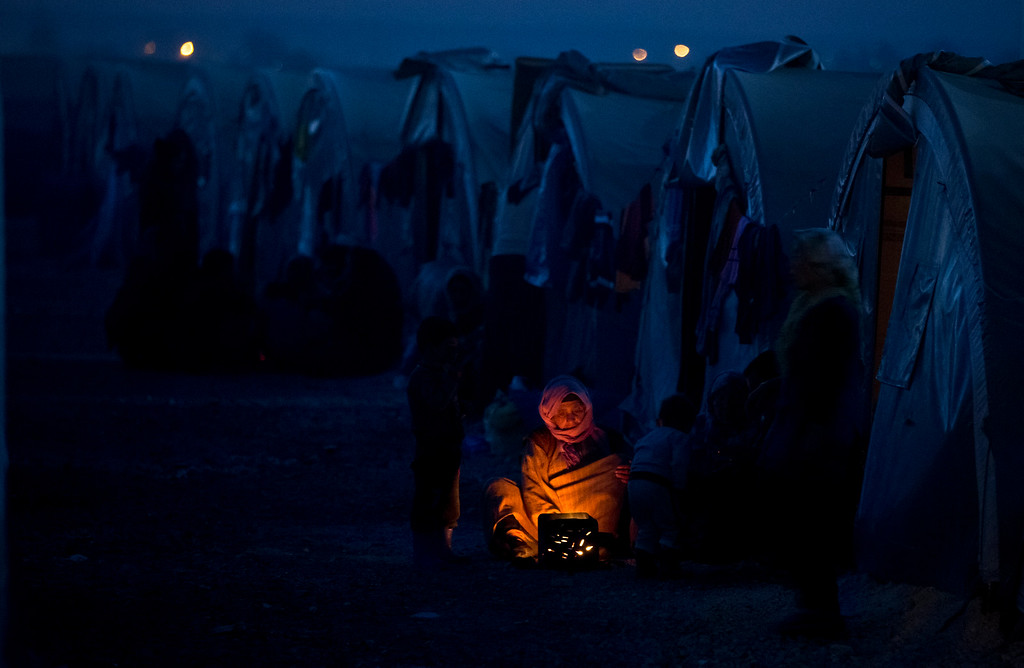 . An elderly Syrian Kurdish refugee woman from the Kobani area, warms up by a fire at a  camp in Suruc, on the Turkey-Syria border Monday, Nov. 10, 2014. Kobani, also known as Ayn Arab, and its surrounding areas, has been under assault by extremists of the Islamic State group since mid-September and is being defended by Kurdish fighters. (AP Photo/Vadim Ghirda, File)