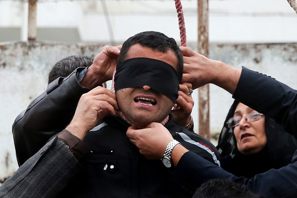 . This picture provided by ISNA, a semi-official news agency, taken on Tuesday, April 15, 2014 shows Maryam Hosseinzadeh, right, and her husband Abdolghani, left, removing the noose from the neck of blindfolded Bilal who was convicted of murdering their son Abdollah in the northern city of Nour, Iran. Bilal who was convicted of killing Abdollah Hosseinzadeh, was pardoned by the victim\'s family moments before being executed. (AP Photo/ISNA, Arash Khamoushi, File)