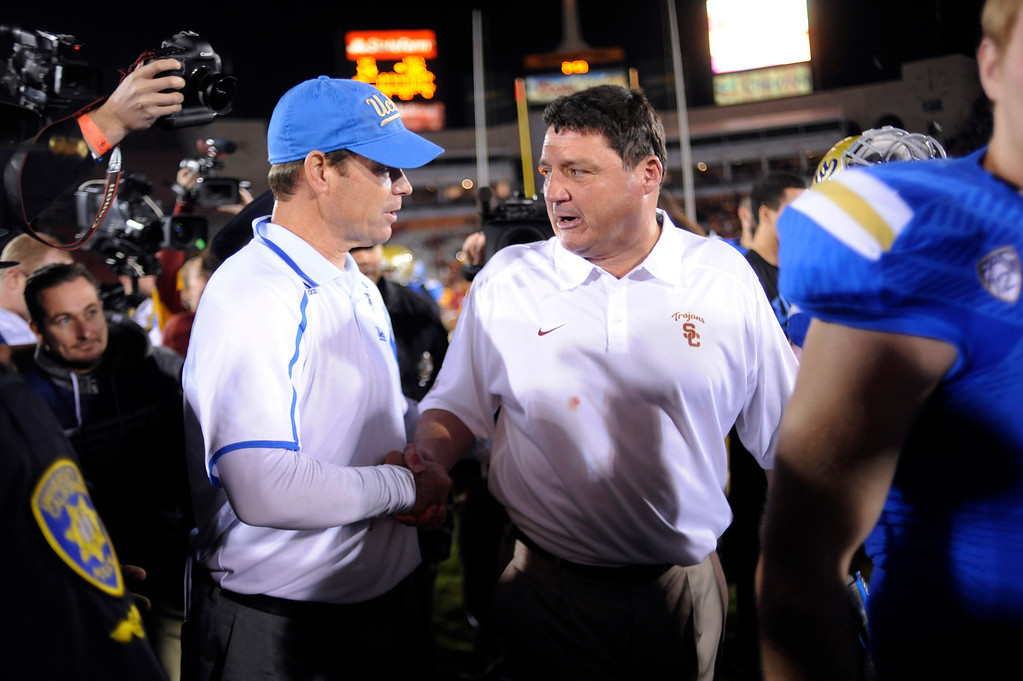 . USC interim head coach Ed Orgeron and UCLA head coach Jim Mora shake hands after their game at the Los Angeles Memorial Coliseum Saturday, November 30, 2013.  UCLA beat USC 35-14. (Photo by Hans Gutknecht/Los Angeles Daily News)