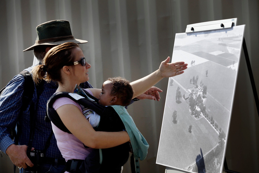 . Duane Stevens, daughter, Daniela Tanner and 9-month-old grandson, Abel Tanner, study a 1940\'s photo during a groundbreaking ceremony for Martial Cottle Park in south San Jose, Calif. on Friday, Aug. 9, 2013. Official ground breaking took place today on what will be a new state and county park that will showcase the rich agricultural history of Silicon Valley. The 287 acres is one of the last working farms in San Jose and his been a farm for the past 150 years. (Gary Reyes/Bay Area News Group)